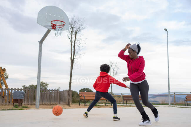 Full length of happy mother playing basketball with her son on outdoor basketball court — Stock Photo