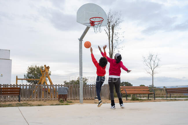Mother and son having fun on outdoor basketball court — Stock Photo
