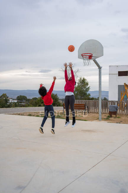 Black mother and son playing basketball on court outdoors — Stock Photo