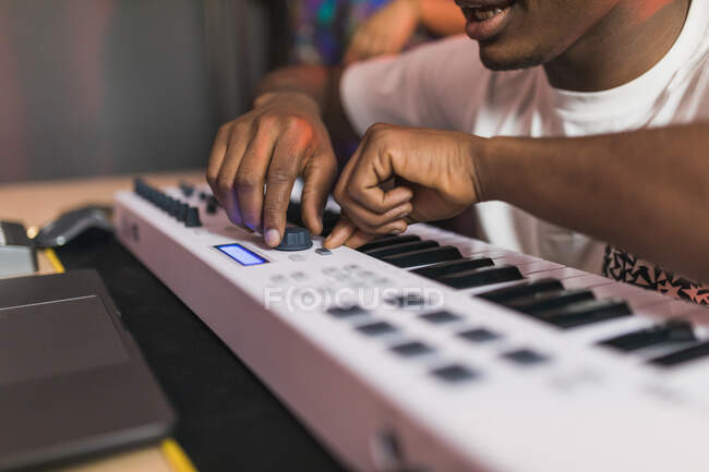 Side view of young African American partners using netbook with sound recording software on screen in music studio — Stock Photo