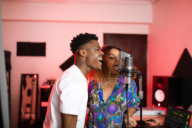 Young African American vocalists with Afro hairstyle and closed eyes singing into professional microphone — Stock Photo