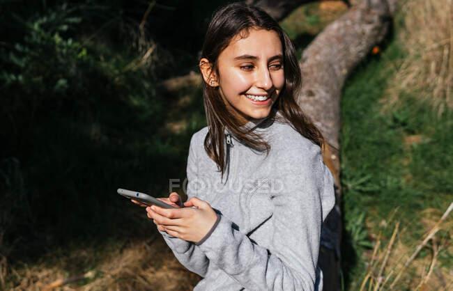 Позитивная молодая женщина-туристка в спортивной одежде сидит на стволе дерева и проверяет маршрут на мобильном телефоне, проводя солнечный день в зеленом лесу и отворачиваясь — стоковое фото