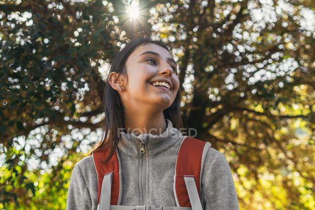 Щаслива оптимістична молода самотня мандрівниця в активаціях з рюкзаком насолоджується подорожю в зеленому лісі в сонячний день. — стокове фото