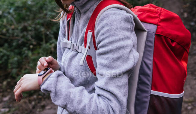 Seitenansicht einer Nutzpflanze in Aktivkleidung mit Rucksack mittels GPS auf Fitness-Tracker zur Navigation beim Wandern im Wald — Stockfoto