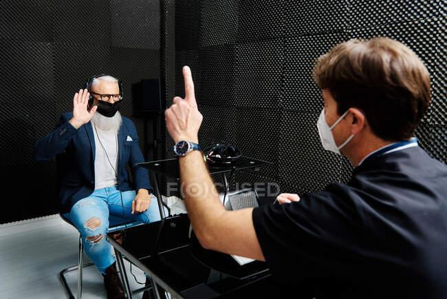 Maschio anziano in cuffia e maschera seduto in camera con medico che conduce diagnosi audiologica dell'udito — Foto stock