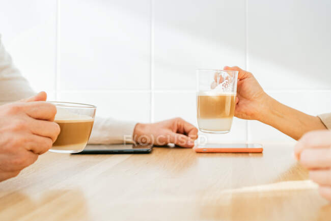 Side view of cropped unrecognizable adult couple sitting at counter in kitchen and enjoying aromatic coffee while having breakfast at home — Stock Photo