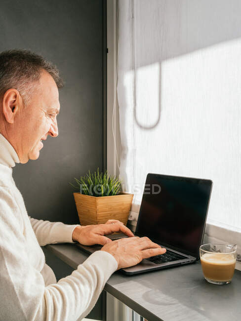 Side view of smiling middle aged male working on counter with netbook and cup of coffee in kitchen in the morning — Stock Photo