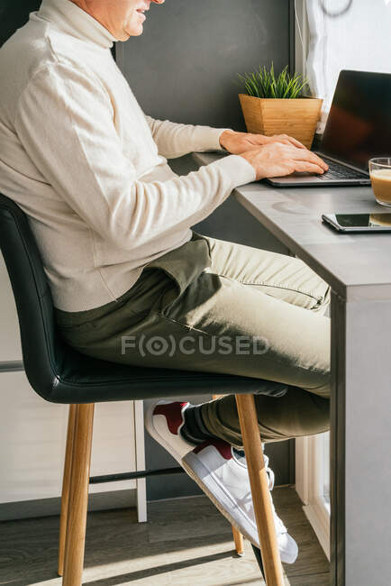Side view of cropped unrecognizable middle aged male working on counter with netbook and cup of coffee in kitchen in the morning — Stock Photo
