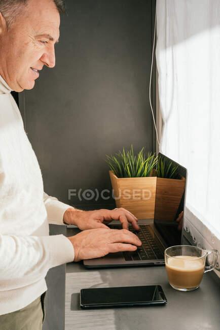Seitenansicht eines lächelnden Mannes mittleren Alters, der am Tresen mit Netbook und Tasse Kaffee in der Küche am Morgen arbeitet — Stockfoto