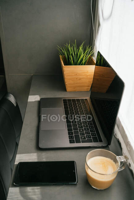 Ordinateur portable moderne et smartphone placés sur le comptoir avec tasse de café du matin dans la cuisine éclairée par la lumière du soleil — Photo de stock