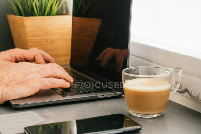 Cropped unrecognizable middle aged male working on counter with netbook and cup of coffee in kitchen in the morning — Stock Photo