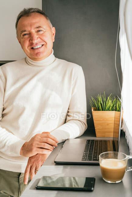 Lächelnder Mann mittleren Alters lehnt am Tresen mit Netbook und Tasse Kaffee, während er morgens in der Küche steht und in die Kamera schaut — Stockfoto