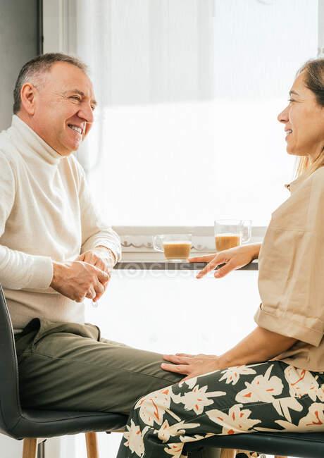 Вигляд дорослої пари, що сидить за прилавком на кухні і насолоджується ароматичною кавою, коли снідає і дивиться один на одного. — стокове фото