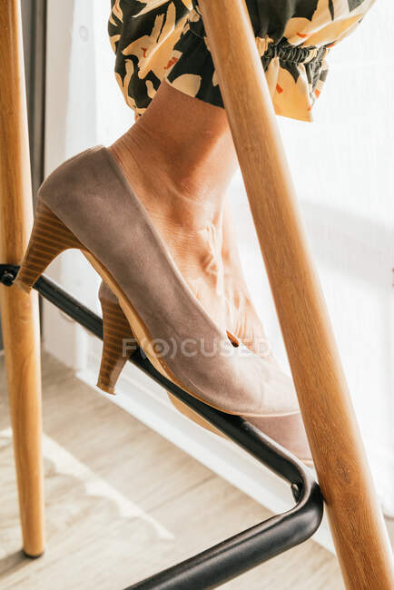 Leg of crop unrecognizable mature female in kitten heeled shoes sitting on stool at home — Stock Photo