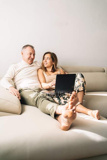 Coppia sorridente di mezza età che si coccola sul divano in soggiorno e guarda film su netbook mentre si rilassa a casa nel fine settimana — Foto stock