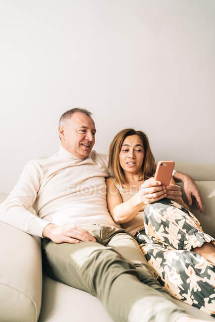 Lächelndes Paar mittleren Alters kuschelt auf Sofa im Wohnzimmer und surft auf Smartphone, während es sich am Wochenende zu Hause entspannt — Stockfoto