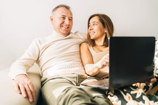 Lächelndes Paar mittleren Alters kuschelt auf Sofa im Wohnzimmer und schaut Film auf Netbook, während es sich zu Hause am Wochenende entspannt — Stockfoto