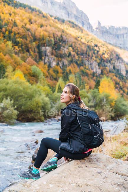 Самка з рюкзаком сидить на валуні поблизу річки в горах Піренеїв під час відпочинку в Національному парку Ордеса - і - Монте - Пердідо. — стокове фото