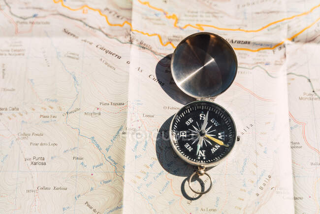 From above of retro compass placed on paper map showing concept of navigation and traveling — Stock Photo