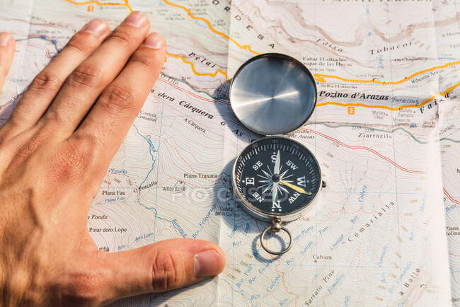 From above of anonymous crop traveler orientating on paper map and compass during vacation in Ordesa y Monte Perdido National Park on sunny day — Stock Photo