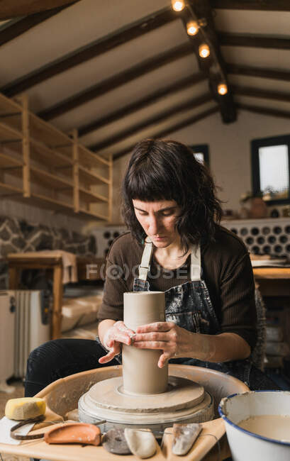 Focused female artisan creating clay tableware on pottery wheel while working in art studio — Stock Photo