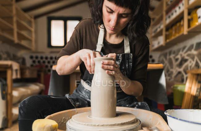 Konzentrierte Kunsthandwerkerin kreiert Tongeschirr auf Töpferscheibe bei der Arbeit im Kunstatelier — Stockfoto