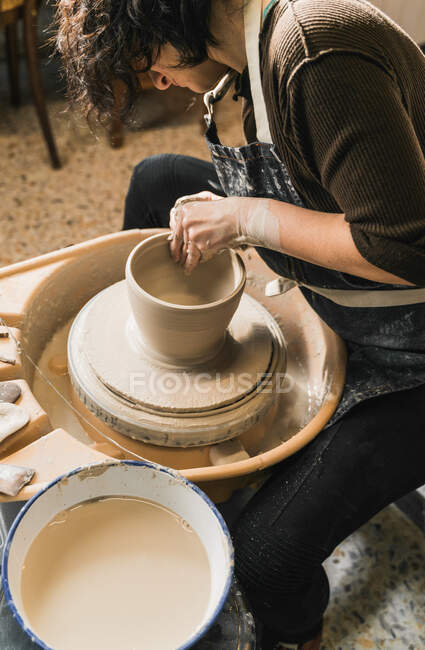 Side view of focused unrecognizable female artisan using pottery wheel and creating handmade earthenware in workshop — Stock Photo
