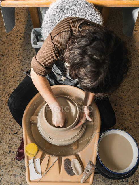 From above of anonymous female artisan using pottery wheel and creating handmade earthenware in workshop — Stock Photo