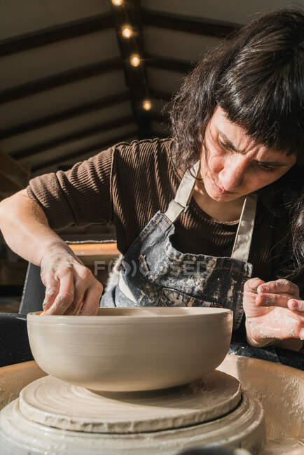 Focused female artisan using pottery wheel and creating handmade earthenware in workshop — Stock Photo