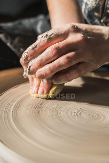 Crop unrecognizable craftswoman creating earthenware on pottery wheel in studio — Stock Photo