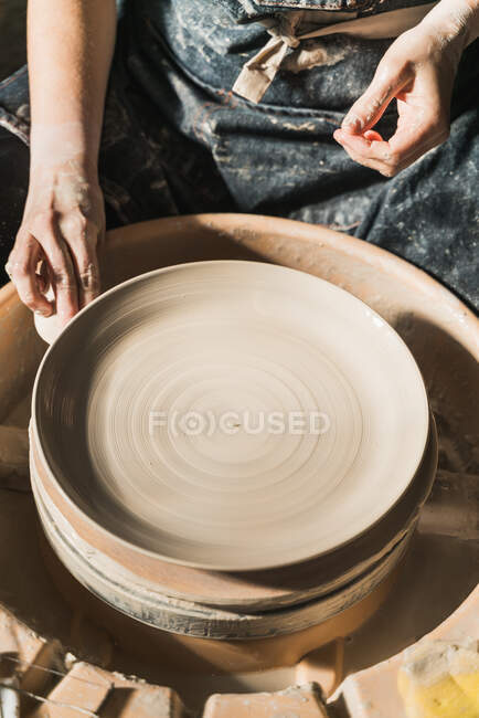 From above of crop unrecognizable craftswoman creating earthenware on pottery wheel in studio — Stock Photo