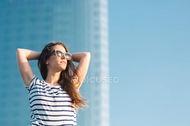 Low angle of cheerful carefree young female in sunglasses wearing casual striped t shirt and jeans enjoying sunny summer day — Stock Photo