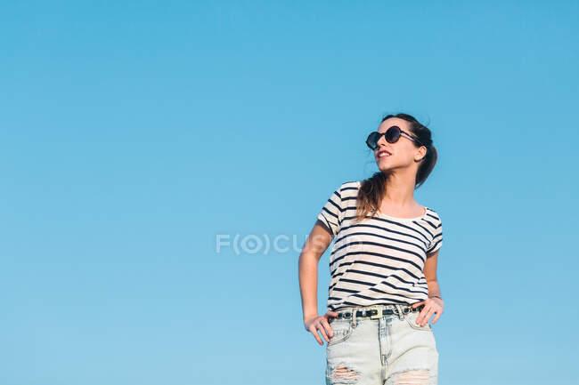 Baixo ângulo de alegre despreocupado jovem fêmea em óculos de sol vestindo camisa listrada casual e jeans desfrutando de dia ensolarado de verão — Fotografia de Stock