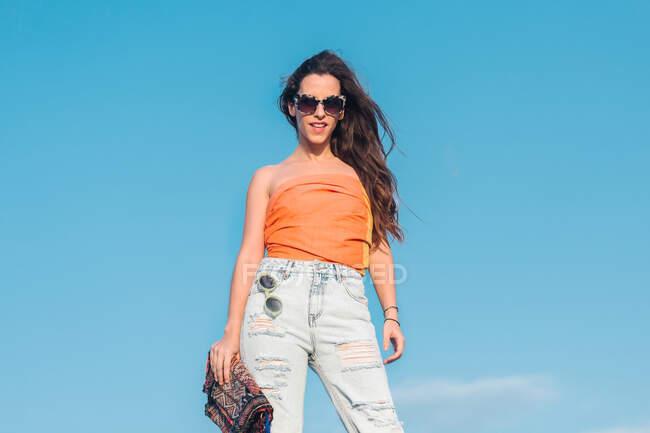 Niedrige Winkel der fröhlichen jungen langhaarige Frau in trendigen Sonnenbrille trägt Sommer-Top und Jeans mit stilvoller Handtasche, während sie gegen den blauen Himmel stehen — Stockfoto