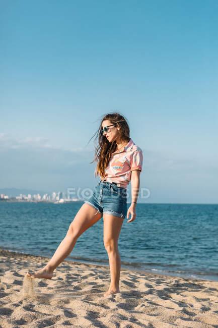 Corps complet de jeune femme pieds nus en tenue décontractée tendance et lunettes de soleil jouant avec le sable sur la plage près de la mer dans une journée d'été ensoleillée — Photo de stock