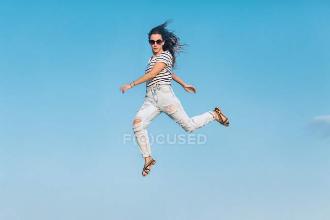 Desde abajo todo el cuerpo de la moderna mujer hipster en gafas de sol con camisa a rayas y vaqueros rasgados con estilo saltando alto contra el cielo azul - foto de stock