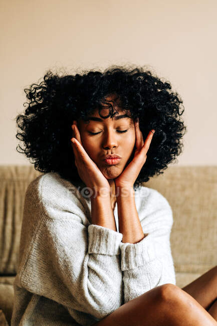 Gentle African American female in sweater and with Afro hairstyle showing duck face with closed eyes at home — Stock Photo