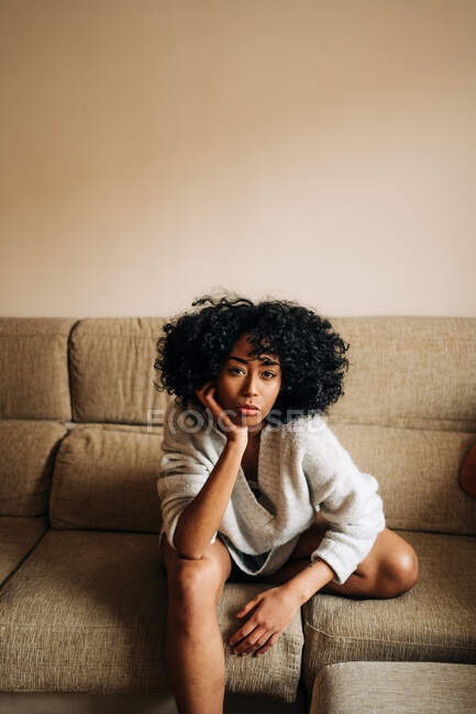 Confident African American female with curly hair sitting on couch and leaning on hand while looking at camera at home — Stock Photo