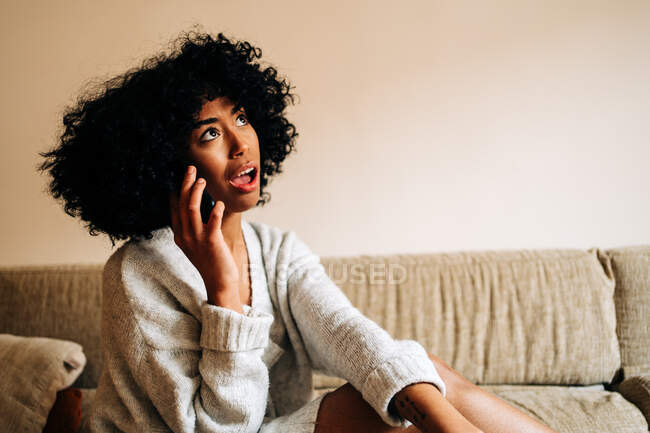 African American female sitting on sofa and talking on mobile phone at home while looking up — Stock Photo