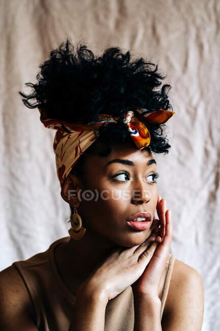Спокійна чорна жінка в модному головах і з африканською зачіскою, що спирається на руки і дивиться на бежеве тло — стокове фото
