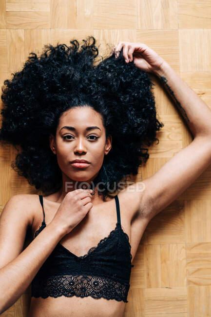 Сверху тонкая афроамериканка с вьющимися волосами, лежащими на паркетном полу и смотрящими в камеру — стоковое фото