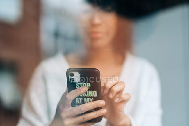 Через стекло черной женщины, отправляющей сообщения в социальных сетях через смартфон дома — стоковое фото