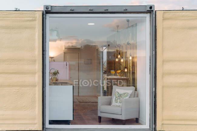 Маленька стильна кухня і зручне крісло за скляною стіною сучасного контейнерного будинку в денний час — стокове фото