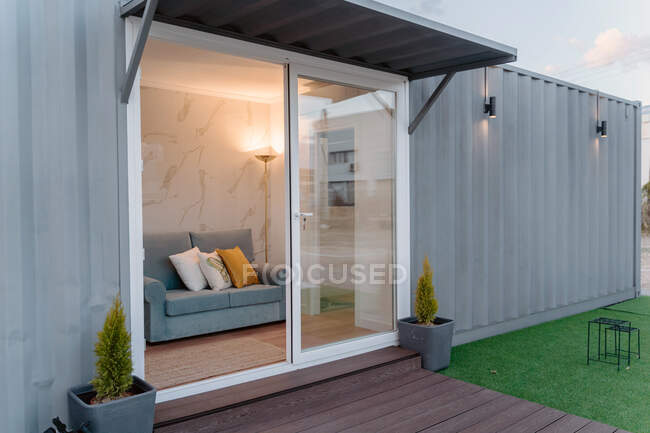 Contemporary gray container house with comfy sofa behind glass door located on grassy yard — Stock Photo