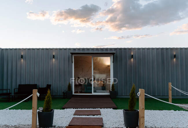 Modern gray shipping container house with glass doors located on grassy meadow and decorated with lush potted plants — Stock Photo