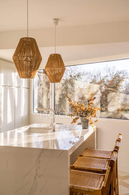 Interior of dining zone in cozy light kitchen with wicker bamboo lamps hanging over table with wooden chairs placed near window — Stock Photo