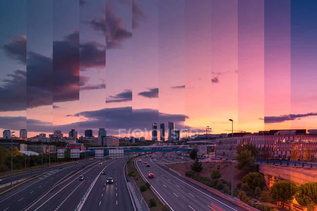 Gratte-ciel contemporain et maisons à étages extérieurs contre la chaussée et les poteaux lumineux brillants à Madrid au coucher du soleil — Photo de stock