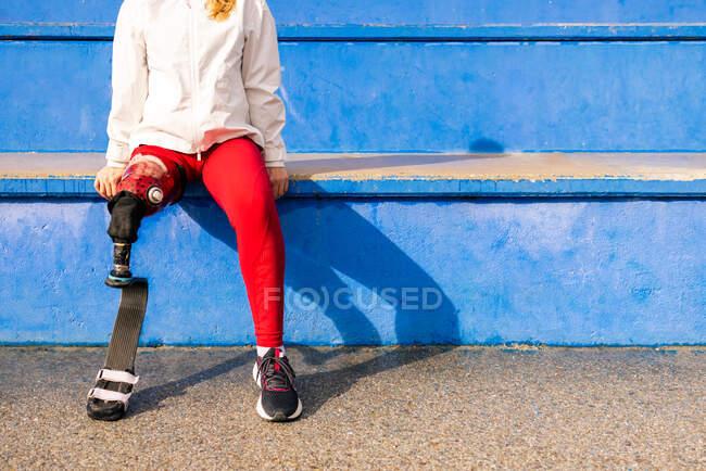 Erkälteter Profiläufer mit Beinprothese sitzt bei sonnigem Tag beim Training im Stadion — Stockfoto