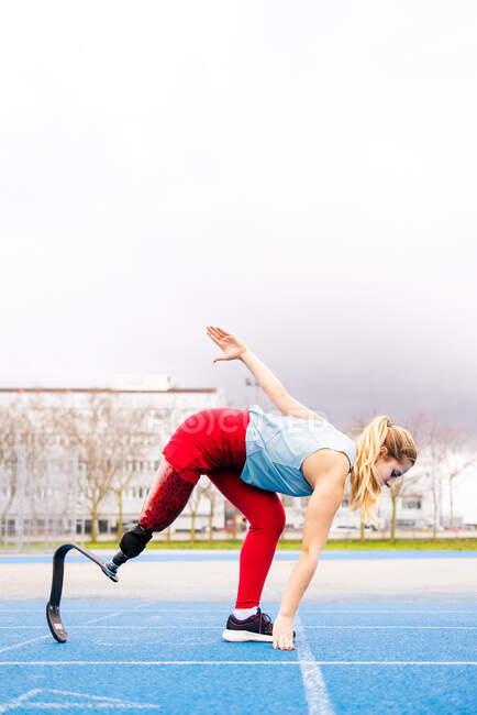 Енергійна спортсменка з протезом ноги приготовлена для старту перегонів на стадіоні.. — стокове фото
