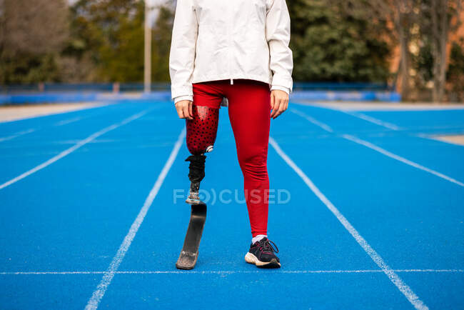 Unrecognizable female athlete in sportswear standing at stadium on sunny day — Stock Photo